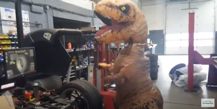 T-rex working on a car